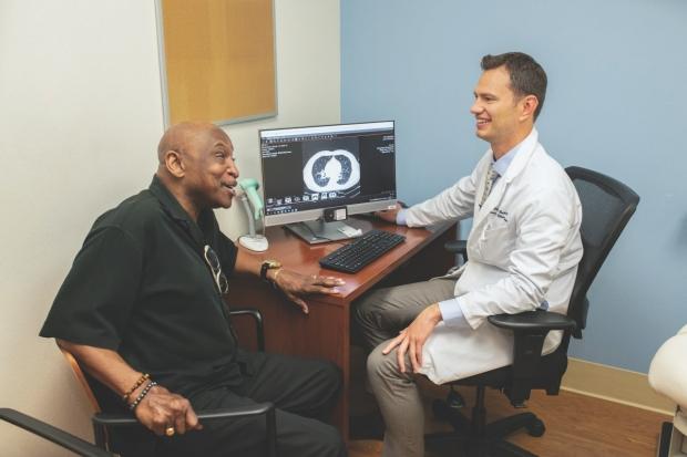 Matt Baker, MD, MS (right), talks with a patient.
