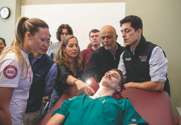 Errol Ozdalga, MD (far right), and Abraham Verghese, MD (holding iPhone), demonstrate one of the Stanford 25 physical diagnosis skills to a group of attentive residents.