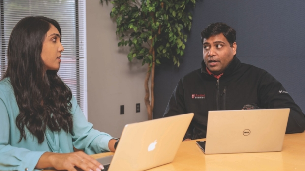 Apple Heart Study Project Manager NISHA TALATI, MBA (left), reviews data with AMOL RAJMANE, MD,