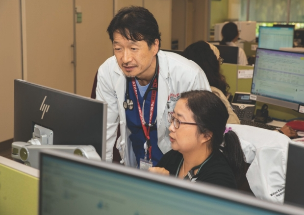 RAY KIM, MD (left), works with a team cell member.